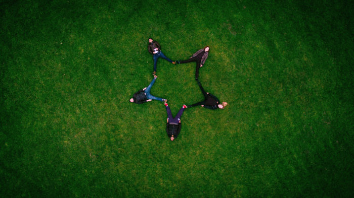 5 people in the grass, legs outstretched creating a star shape